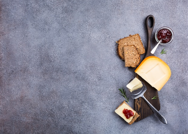 Delicious dutch gouda cheese with cheese slices, multigrain bread, strawberry jam