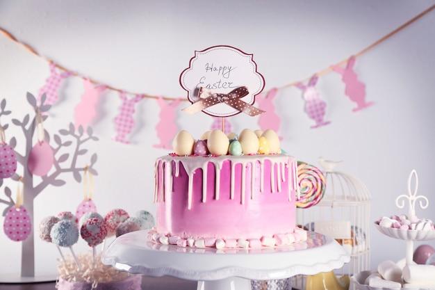 Вкусный кулич, украшенный разноцветными сладкими яйцами и поздравительной открыткой на подставке