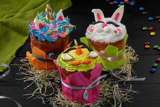 여러 가지 빛깔의 종이 덮개로 싸인 맛있는 부활절 케이크는 검은색 나무 탁자에 있는 건초 위에 있는 유니콘, 닭고기, 토끼 모양의 화려한 달걀 흰자로 장식되어 있습니다. 멋진 축제 구운 식품