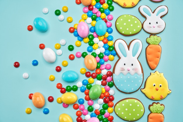 Delicious easter cookies and candies on blue background