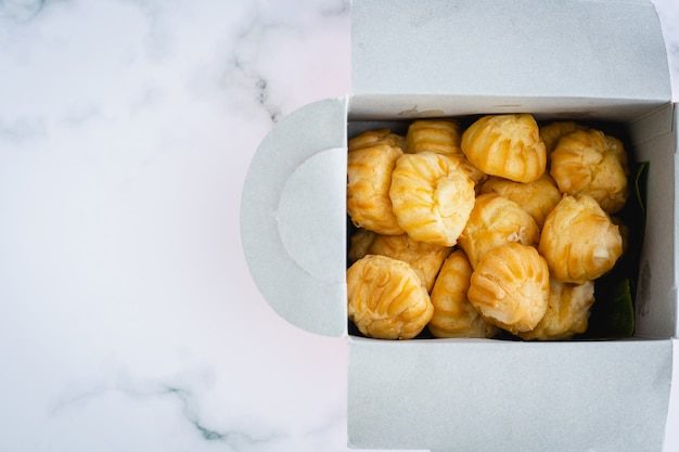 美味しいエクレアバニラクリーム、クリーム、自家製のベーカリーがスナックを食べる概念の白い大理石の背景に紙箱の包装でいっぱいのシュー生地