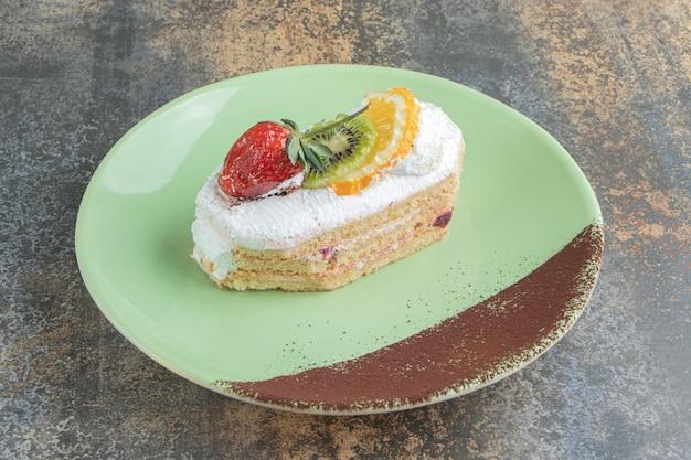 Un delizioso eclair con frutta su un piatto verde