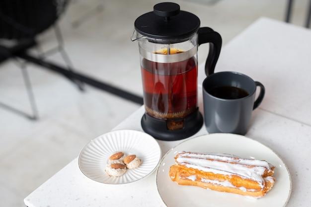 ホワイトクリームとマカロンのおいしいエクレア。急須の紅茶。カフェで甘い食べ物。