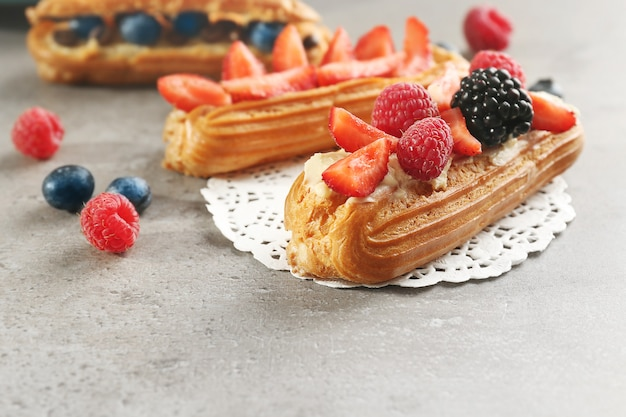 Delicious eclairs with berries and doily on table