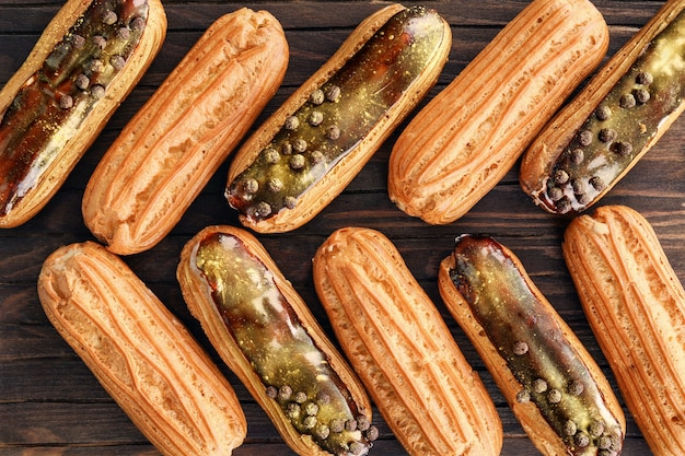 Delicious eclairs on wooden cutting board closeup