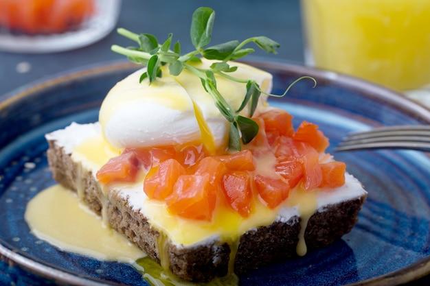 Вкусное яйцо бенедикт с кусочками копченого лосося на завтрак, на синей тарелке, апельсиновый сок в стакане. крупный план, темно-синий фон