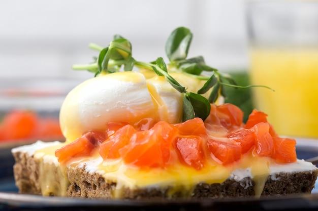 Вкусное яйцо бенедикт с кусочками копченого лосося на завтрак, на столе, апельсиновый сок в стакане. крупный план.