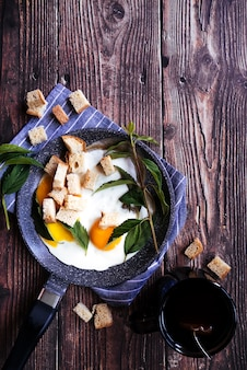 Delicious eggs and tea breakfast on wooden table