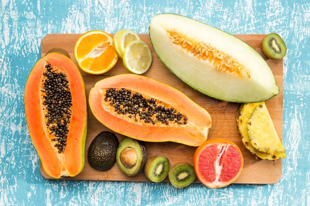 Delicious exotic fruits on wooden board