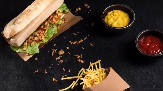 Delizioso hot dog fast-food su carta da forno e condimenti