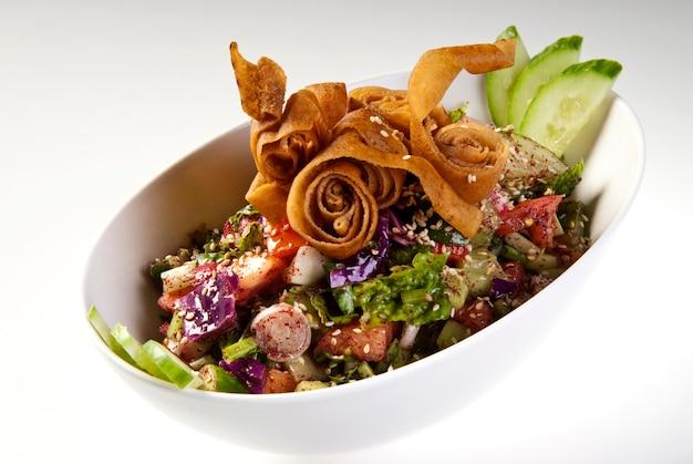 白いプレートにピタクルトン、新鮮な野菜とハーブを添えたおいしいファットーシュまたはアラブサラダ。中東のパンサラダ。簡単で健康的な本物のレシピ