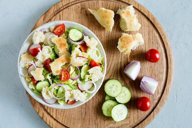 Вкусный салат fattoush с лавашом хлеба, свежими овощами и базиликом на тарелке на деревянной подставке. традиционная ближневосточная или арабская кухня. крупным планом, плоская планировка, светлый фон.