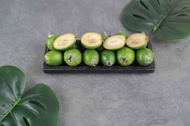 Вкусные плоды фейхоа на черной тарелке. фото высокого качества