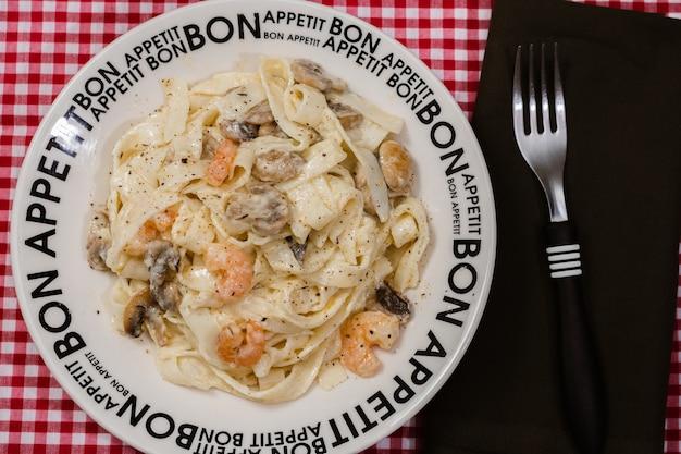 빨간 체크 무늬 식탁보와 함께 bon appetite라고 적힌 접시에 버섯과 새우 크림 소스를 곁들인 맛있는 페투치니. 이탈리아 요리.