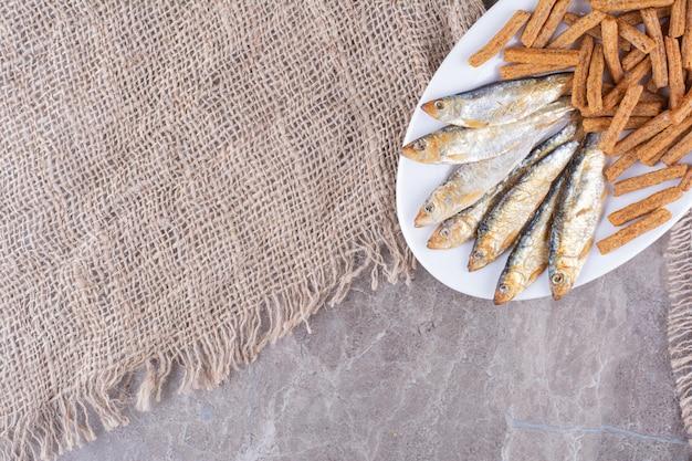Вкусная рыба и крекеры на белой тарелке. фото высокого качества