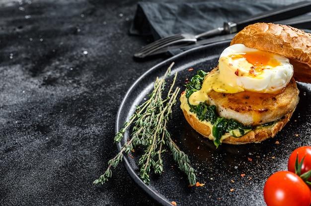 Вкусный рыбный бургер с рыбным филе, яйцом и шпинатом на булочке бриошь