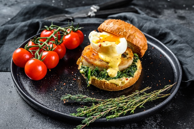 Delicious fish burger with fish fillet, egg and spinach on a brioche bun