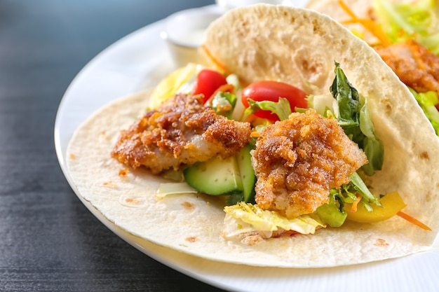 Вкусные рыбные тако на белой тарелке, крупным планом