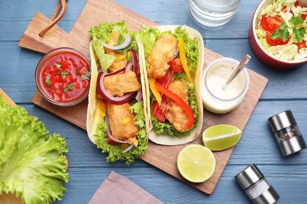 Вкусные рыбные тако на синем деревянном столе, плоская планировка
