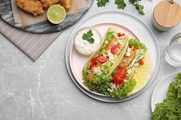 Вкусные рыбные тако на сером мраморном столе, плоская планировка