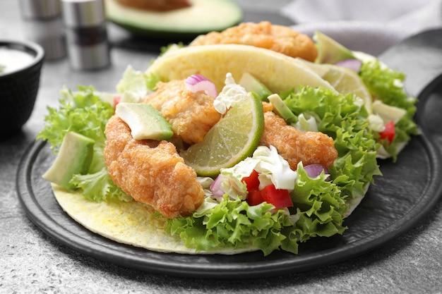 Вкусные рыбные тако на сером столе, крупным планом