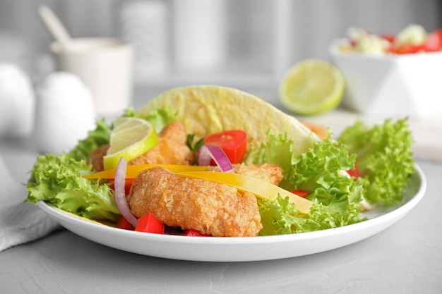 Вкусные рыбные тако на светло-сером столе, крупным планом