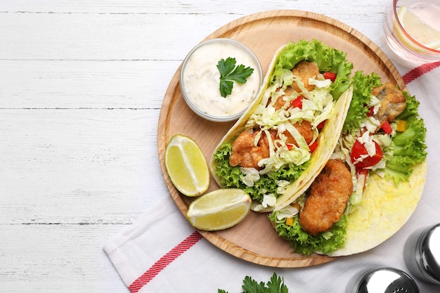 Вкусные рыбные тако на белом деревянном столе, плоская планировка