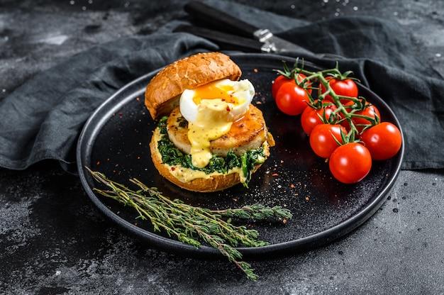 Вкусный фишбургер с рыбным филе, яйцом и шпинатом на булочке бриошь