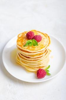 白い大理石の背景にプレートにおいしいふわふわ黄金のパンケーキ