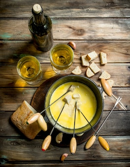Delicious fondue cheese with bread slices and white wine. on a wooden background.