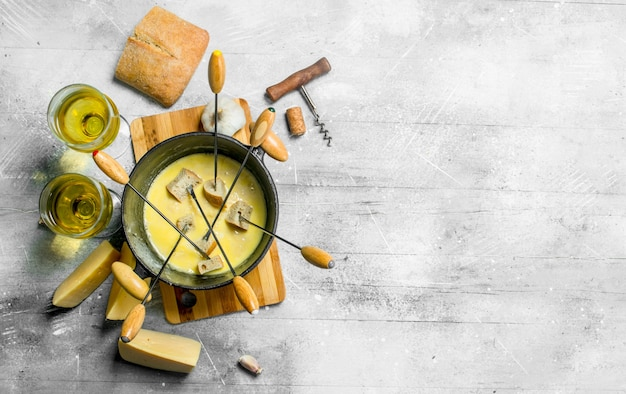 Delicious fondue cheese with bread and white wine . on rustic background