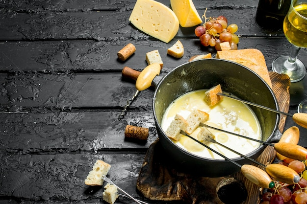 Delicious fondue cheese with white wine on black rustic table..