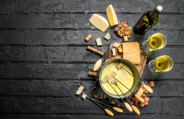 Delicious fondue cheese with white wine. on black rustic.