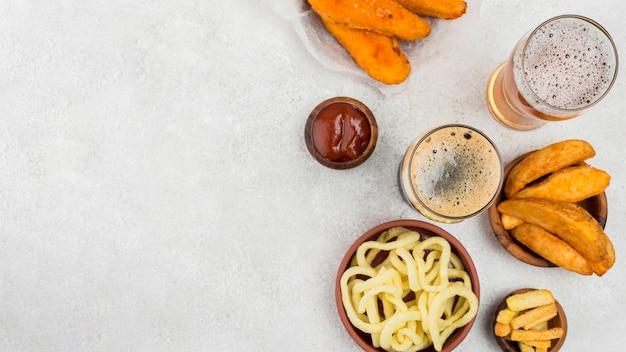 Вкусная еда и пивные бокалы вид сверху