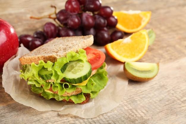 Вкусная еда и фрукты на деревянном столе