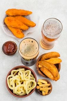 Cibo delizioso e bicchieri da birra piatti laici