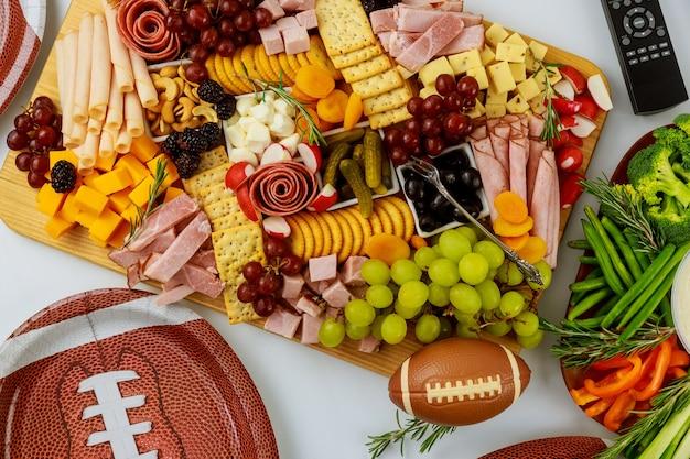 テレビチャンネルでスポーツを見るためのリモコン付きのアメリカンフットボールのゲームパーティーのためのおいしい料理。