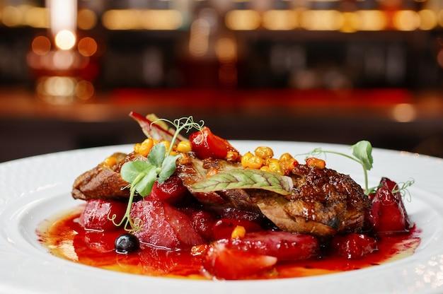 バーの壁にある白いプレートに肉や野菜のおいしい料理