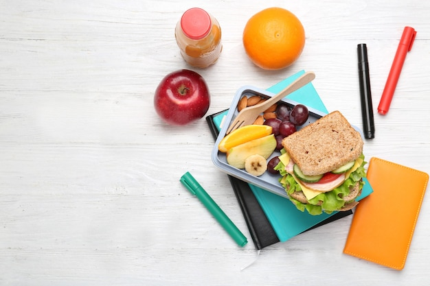 Delicious food in lunch box and stationery on white wooden space