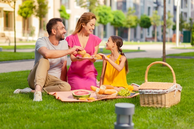 Delicious food. nice happy father and daughter smiling while taking hamburgers from the plate