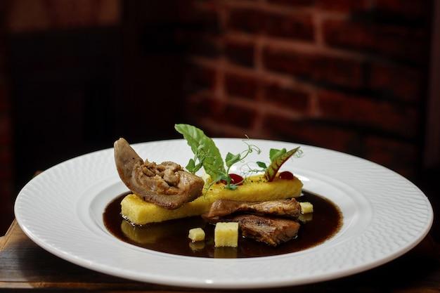 木製の暗いテーブルの上の白いプレートのソースでアヒルのおいしい料理