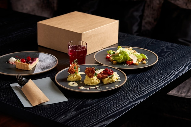 Вкусная еда на столе в богатом ресторане, салат из свежих овощей, кусок торта и бокал напитка, идеально оформленный