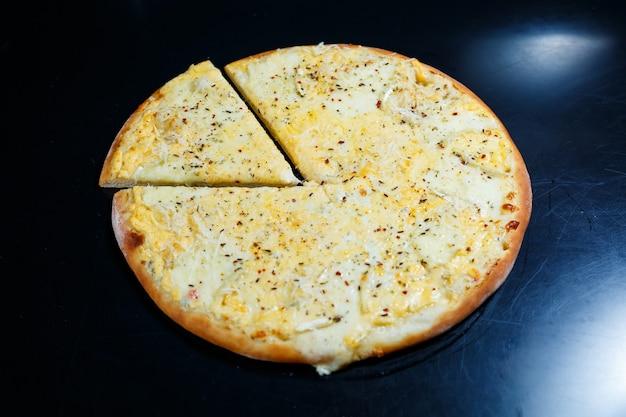 黒の背景にチェダー、パルメザンチーズ、モッツァレラチーズ、トマトソースが入ったおいしいフォーチーズピザ。上からの眺め。