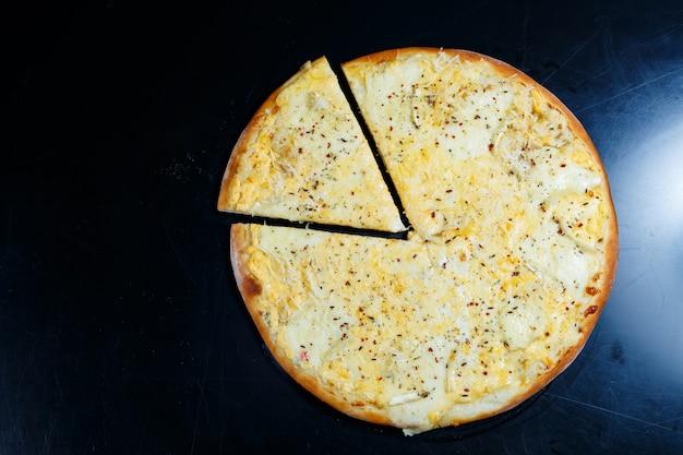 검은색 바탕에 체다, 파마산, 모짜렐라, 토마토 소스를 곁들인 맛있는 4가지 치즈 피자. 위에서 볼 수 있습니다.