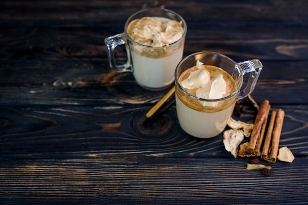 Delicious and fragrant dalgona coffee in glass cups, cinnamon sticks, dried mushrooms, a spoon of instant coffee, sugar.