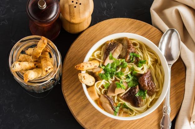 Вкусный ароматный суп из белых грибов в миске на круглой деревянной подставке. вид сверху. черный фон.