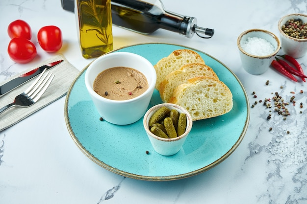 Delicious french appetizer - chicken pate with pickled cucumbers and croutons in a blue plate on a marble surface