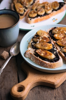 Delicious french breakfast - toast with chocolate and fried bananas on wooden background