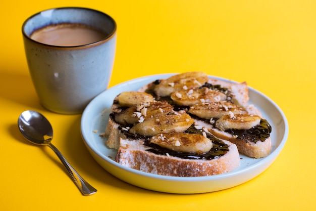 Delicious french breakfast - toast with chocolate and fried bananas on yellow background