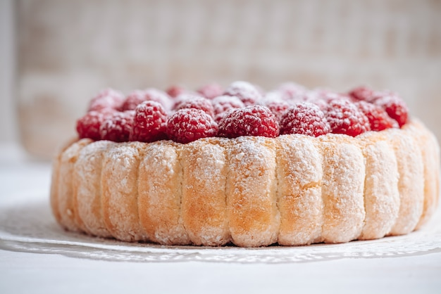 Delicious french charlotte cake with raspberries and savoiardi biscuits
